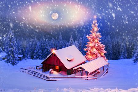 ブリザードでは、ウクライナのカルパチア山脈の草原が羊飼いを覆われています。黄金光納屋および家の羊飼い - 寒い冬と山の峰の背景に霜を美し 報道画像