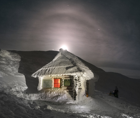 Ukraine, Vorohta- 07, January, 2015: House rescuers after a strong storm. Cabin - a refuge for those in trouble extreme - athletes on the ridge of Montenegro. The moon rose above the top of Hoverla, visible halo