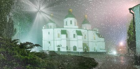 enveloped: Blizzard and rain enveloped Kiev, bad weather a bad review - a romantic mood in the ancient St. Sophia Cathedral, on the background of the ancient walls and trees bashen- monastic park and garden, beautiful illumination at night Stock Photo