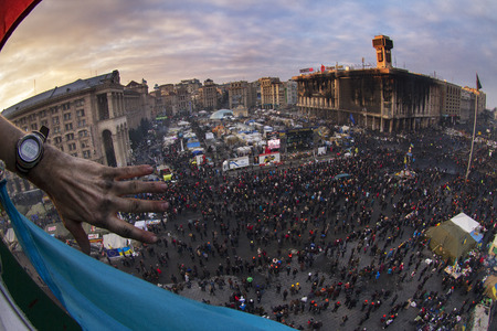 Kiev, Ukraine - February 20, 2014: Freed from government troops Evromaydan. View from the Christmas tree. Seen eagles building set on fire unions. In the background, the people of Kiev, the capital defenders