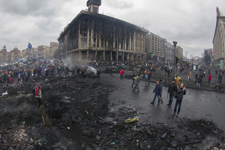 protesters: Kiev, Ukraine - February 20, 2014: Freed from government troops Evromaydan. The smoke protesters hiding from snipers, collecting stones and bottles at the devastated area to the forward position