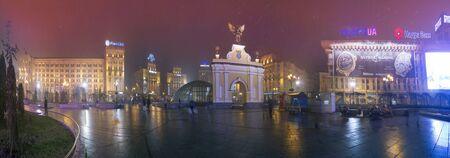 angel de la independencia: Kiev, Ucrania - 23 de noviembre de 2013: Todo el año panorama Plaza de la Independencia, zona de Maidan. Vista del arco del triunfo con un ángel negro, hogar de los sindicatos y la oficina de correos ... peatones caminando bajo la lluvia Editorial