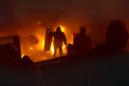 maidan: Kiev, Ukraine - January 22, 2014: Among the flame burning wheels rebel fighters try to contain the offensive by government forces on the street Hrushevskoho burn buses and trucks police