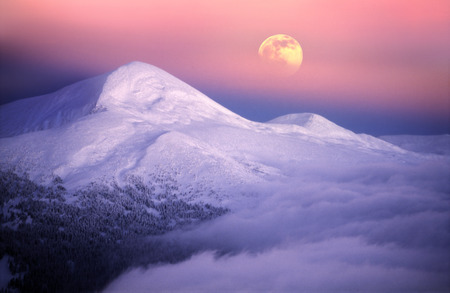 Moonrise among alpine peaks, unforgettable beauty of the spectacle, worth dangerous night-climbing in winter. Goverla-highest point of Ukraine Stock Photo