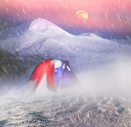 curare teneramente: Sulle cime delle montagne innevate alpinisti e turisti, viaggiatori stabilire tende moderna in tempo complesso proteggono e nutrono la loro vita e la salute, fornendo comfort e la sicurezza della tempesta.