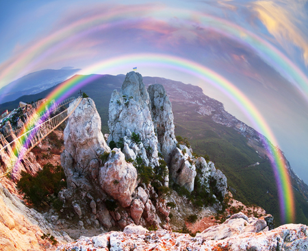 Rocks teeth above Yalta - famous tourist Crimea. After the storm a bright rainbow on a picturesque background of the sea and steep cliffs. On the left is the famous historic a funicular