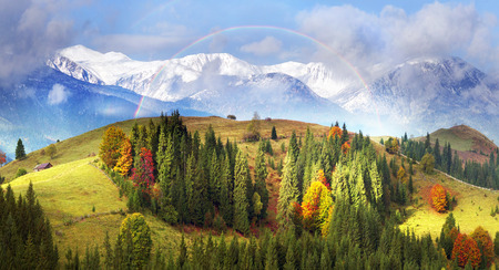Autumn colors of forests over the mountain villages of the Carpathians - Verkhovyna, krivo pole, Dzembronya, amid the cold snowy ridge high ridge Montenegro - the highest in Ukraine