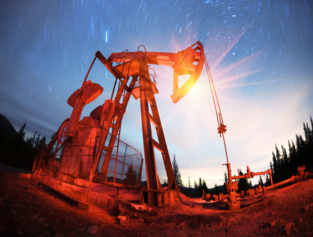 Classic retro Oil pump under the stars on the mountain with illuminated Synechka Oil  gas production in Ukraine an old ancient method of producing hydrocarbons  chemical raw materials Imagens