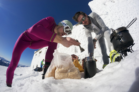 Ukraine, Verkhovyna, February 13, 2015: extreme journey to the top of the mountain to  observatory on Mount Pip Ivan on the background of ice snow, tourists are preparing to drink tea Lunch Stock Photo