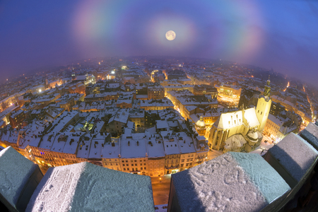 Ukraine, Lviv - January 14, 2017: Panoramic view from the town hall of the tourist city of Lviv with snow blizzard frost on the ancient city with the old residential quarters, Christian temples
