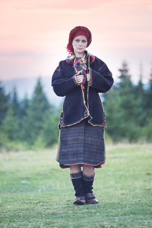 Young Ukrainian girl in an old picturesque present authentic national costume Ukrainian highlanders Gutsul on the background of wild nature Hutsulshchyna in Carpathians, Ukraine