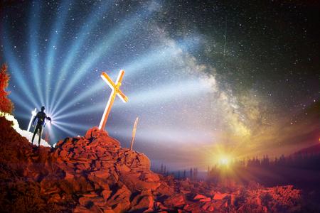 Cruz en el Monte Strymba de madera elevada a la gloria de Dios, Jesucristo. Luz de la noche encendiendo un fuego sobre un fondo de montañas piedras de vegetación alpina bajo las estrellas de la Vía Láctea