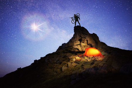 Cyclist overnight. Artistic lighting unreal mountain scenery while rock climbing wild mountains provides a unique fantastic effect unearthly planets with fabulous landscapes  Stock Photo