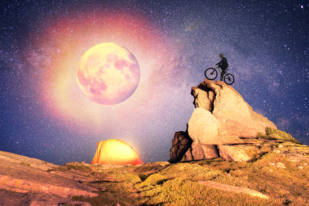 Cyclist overnight. Artistic lighting unreal mountain scenery while rock climbing wild mountains provides a unique fantastic effect unearthly planets with fabulous  alien landscape