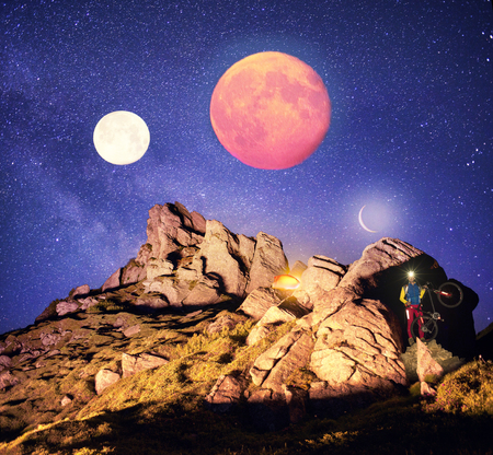 Cyclist overnight. Artistic lighting unreal mountain scenery while rock climbing wild mountains provides a unique fantastic effect unearthly planets with fabulous landscapes of Mars