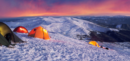 At the highest peak of Ukraine Goverla stands on New Year camp climbers romantic Ukrainian country. Extreme tent buried in snow storms withstand bad weather frost wind alpine peaks Stock Photo