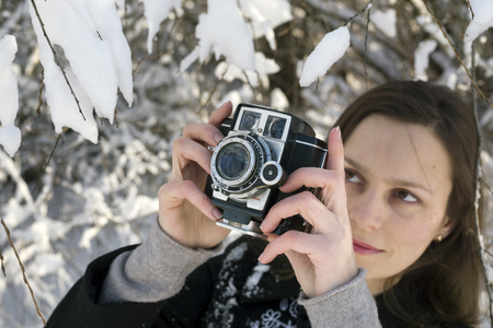Ukraine, Ivano-Frankivsk, December 29, 2014: Young longhaired woman in the old Ukrainian on the background of wild nature in winter frosty weather meadow walks with old film camera