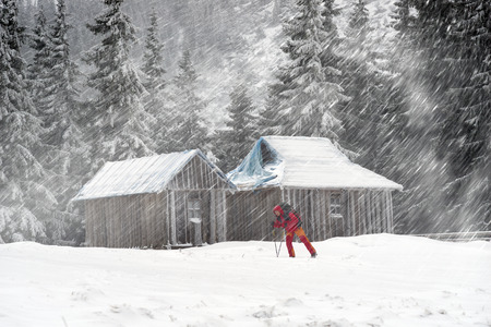 After the storm a strong frost frosted alpine peaks of the Carpathians in Ukraine, and the bright colors of Christmas huts on wild forests of spruce and pine glowing hut window with tourists