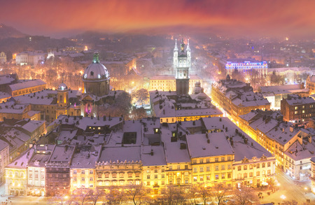Panoramic view from the town hall of the tourist city of Lviv with snow blizzard cold mist on the ancient city with the old residential quarters and Christian churches in the background