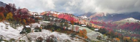 very cold: Cold autumn in Carpathian village. Bright colors after a snowfall blizzard is very beautiful scenic, beech, birch and pine forests and Hutsul houses on background ridge slopes Sokilsky Stock Photo
