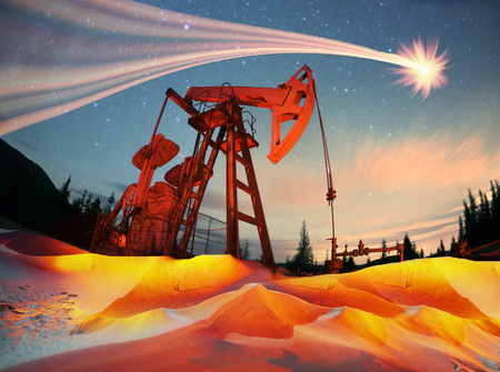 Classic retro Oil pump under the stars on the mountain with illuminated Synechka Oil  gas production in Ukraine an old ancient method of producing hydrocarbons  chemical raw materials Stock Photo