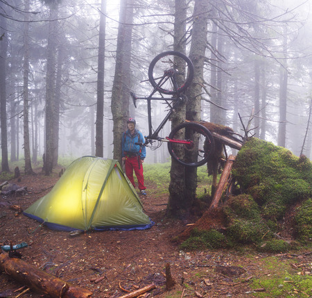 Ukraine, Vorohta-  rain mist rider on a mountain bike prepares for spending the night in a tent near the old hut of moss in the wild alpine spruce forest among the windbreaks