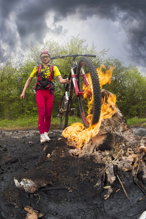 Ukraine, Prykarpattya - in the Carpathians there is an interesting phenomenon of a small mud and flaming volcano in the village of Starunia. Traveler cyclist is photographed in fire flashes