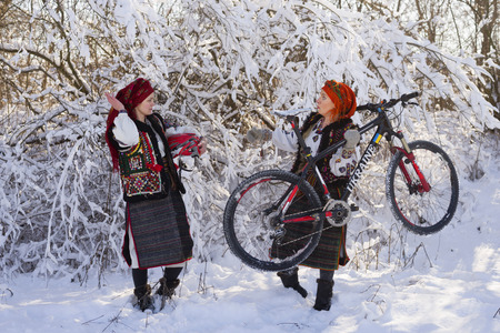 Young Ukrainian girl in an old picturesque present authentic national costume Ukrainian highlanders Gutsuliya with modern technology Hardtail Mountain Bike carbon composite  Ukraine