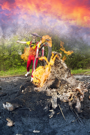 Ukraine, Prykarpattya - in the Carpathians there is an interesting phenomenon of a small mud and flaming volcano in the village of Starunia. A cyclist is photographed in fiery gas flashes Stock Photo