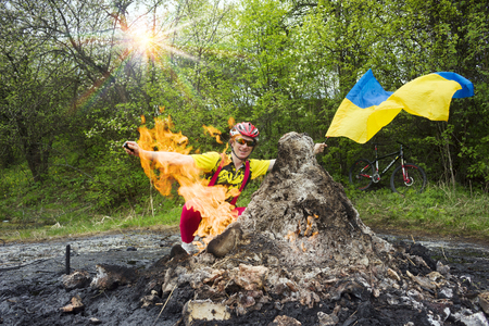 carpathians: Ukraine, Prykarpattya - in the Carpathians there is an interesting phenomenon of a small mud and flaming volcano in the village of Starunia. A cyclist is photographed in fiery gas flashes Stock Photo
