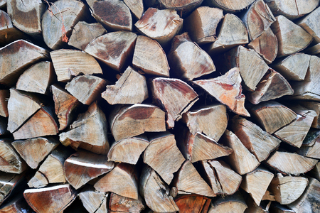 outdoor fireplace: Warehouse a stack of cut chopped sawn natural firewood in a mountain resort A good ecological and economic option for heating houses and hotels in winter and summer