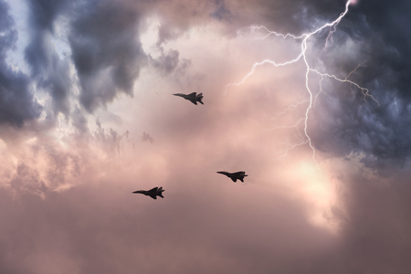 Soviet army fighter in dangerous proximity to thunderstorms in cumulus clouds. Perfect technique is a symbol of military confrontation between countries and cultures of Earth civilization Stock Photo
