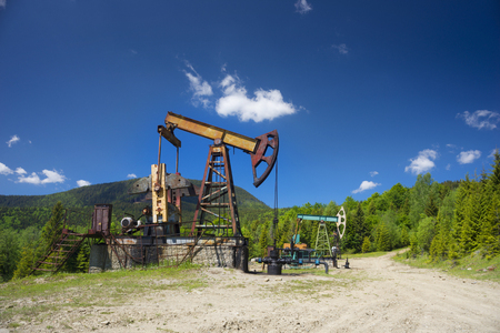 Ancient traditional classical oil pumps of Ukrainian oilmen in the Carpathians and Carpathian Mountains in the Polonies Delyatyn in the background of mountains in sunny weather Standard-Bild
