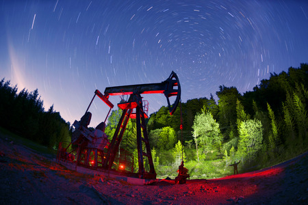 ancient traditional classic oil pumps of Ukrainian oilmen in the Carpathian Mountains on the Delyatyn Polonium are illuminated by colored LED flashlights under the starry sky of the Galaxy Stock Photo