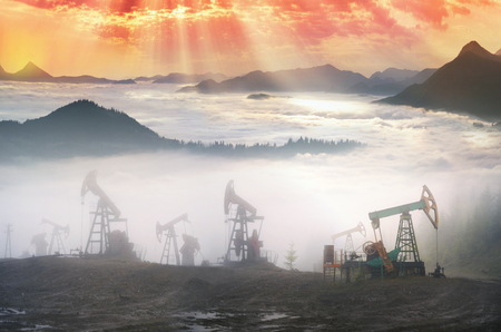 pumping unit: Ukraine, Carpathians old ancient classical Romanian and Soviet oil pumps rocking at dawn amid the damaged ecology of alpine meadows work to produce the energy of the modern world