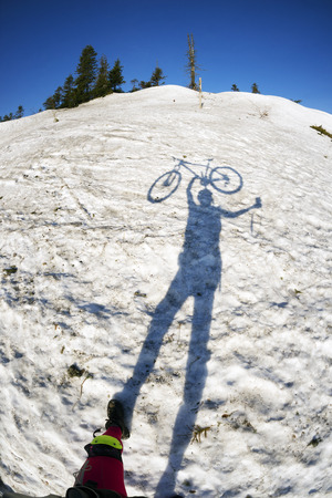 carpathians: Extreme lone racer with a bike and his shadow among the peaks of the Ukrainian Carpathians meets the sunrise skating on the slopes of the ridges on the background of a snow panorama