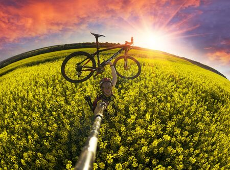 A bike ride on the background of rapeseed fields, a mountain bike and a symbolic combination of colors of the Ukrainian flag, golden and heavenly. Ecological fuel from rape