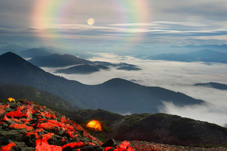 Panorama of the night mountains from the peak of Synyak in the Gorgan Mountains above Bukovel resort. The sea of fog in the valley against the background of high peaks in the moonlight