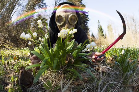 man in a gas mask with knives axes saws the creative symbolizes the civilization coming to the living nature of the flowers of the spring snowdrops. Predatory destruction of protected plants