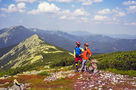 Young racers against the background of wild mountains with the flag of Ukraine. Vertex Synyak extreme trip to a bicycle, a symbol of off-road and dangerous way tourists travel