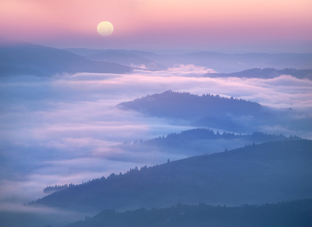 czech switzerland: Western Europe mountainous terrain and alpine villages against the backdrop of the ridges bathe in the sea of fog after the rain on a warm summer morning at dawn in the pink rays