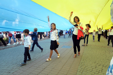Ukraine, Ivano-Frankivsk - August 24, 2017: Independence Day is a state holiday of a sovereign European country. Townspeople in embroidered shirts sweep the gigantic flag of Ukraine