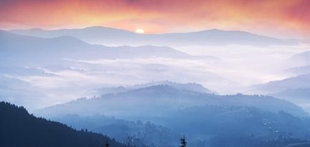 czech switzerland: Europa occidentale terreno montuoso e villaggi alpini sullo sfondo dei ridges bagnano nel mare di nebbia dopo la pioggia in una calda estate mattina all'alba nei raggi rosa