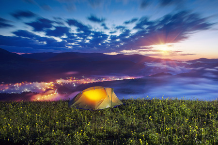 below: tent is illuminated at the top of the mountain, the waves of the misty sea float in the valley against the backdrop of high peaks covered in forests. Below is a mountain village shining