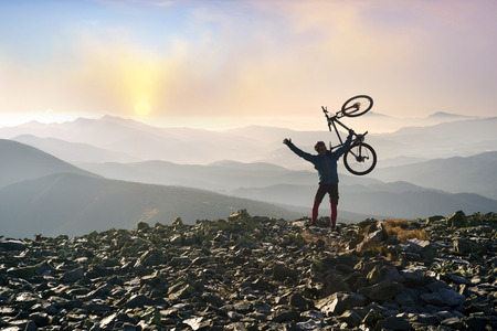 Placers with rocks on the steep Carpathian slope in the morning at sunrise, a lone rider racer climbs the famous legendary peak of Mount Syvul in the Ukrainian Gorgans in Ukraine Stock Photo