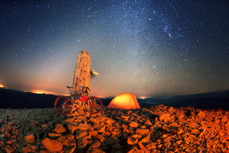 Placers with stones on a steep peak with a stone pillar, a mountain professional bicycle against the background of the Milky Way, the legendary summit of Mount Syvul in Gorgan in Ukraine