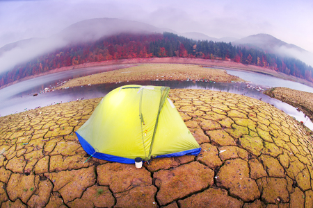 Tent of the extreme traveler on the background of the ecological desert symbolizes human life  world of industrial revolution in countries with a low level of culture of behavior in nature Stock Photo