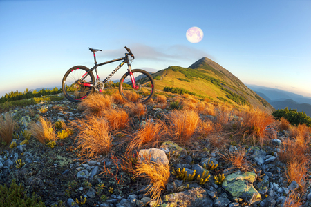 Placer grass similar to a hedgehog with rocks and lichens on a steep slope, a lone rider racer rises to the famous legendary peak of Mount Syvul in the Ukrainian Gorgans in Ukraine Foto de archivo - 91905907