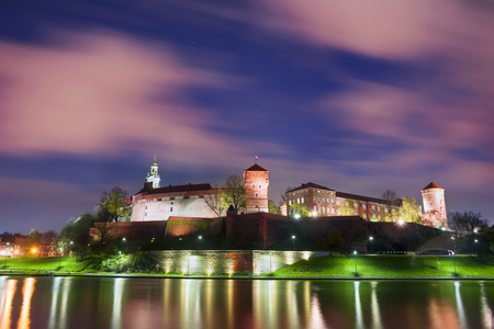 Walk on a rainy evening in the old picturesque embankment of the famous city of Krakow Eastern Europe under the castle of Wawel located on the background  wide Vistula river bank