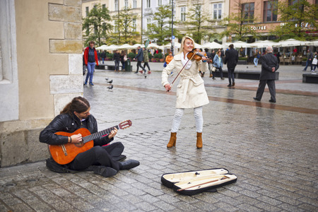 Poland, Krakow, September 14, 2015: Guests of the city, tourists and travelers, townspeople listen to songs in an artistic performance on the ancient Market Square, the main attraction Editorial